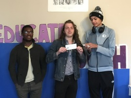Board members Dom and Justin showing the check received from Red Rock. King Howard is present.
